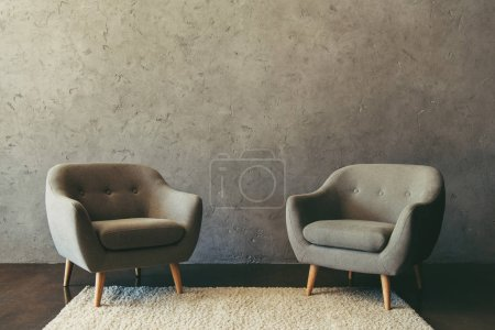 Photo for Interior of modern room with armchairs standing on white rug - Royalty Free Image