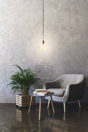 interior of modern room with hanging light bulb, table with books, plant and armchair