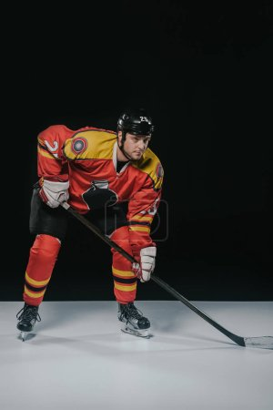 full length view of serious sportsman playing ice hockey and looking away on black