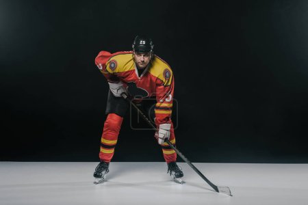 serious sportsman playing ice hockey and looking at camera on black