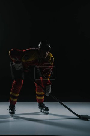 full length view of sportsman in protective sportswear playing ice hockey on black