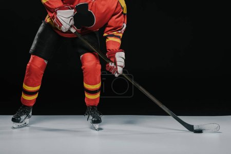cropped shot of sportsman with hockey stick playing ice hockey on black