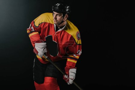 handsome young sportsman holding hockey stick and looking away isolated on black