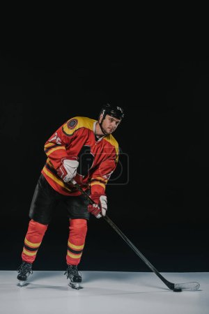 full length view of handsome young sportsman in protective sportswear playing hockey on black