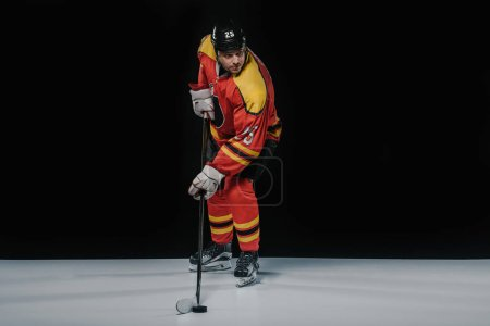 full length view of professional sportsman in skates playing ice hockey on black