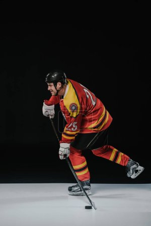 side view of ice hockey player playing hockey and looking away on black