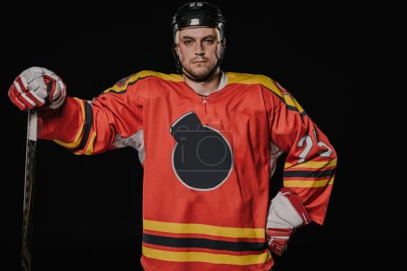 professional ice hockey player standing with hand on waist and looking at camera isolated on black
