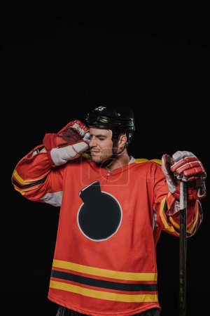 professional hockey player suffering from headache isolated on black