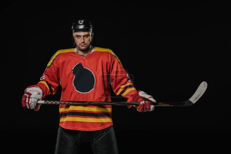 professional ice hockey player holding hockey stick and looking at camera isolated on black