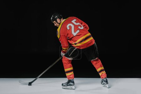 back view of professional sportsman playing ice hockey on black