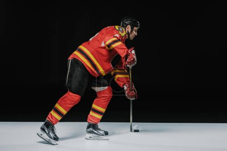 side view of young professional sportsman playing ice hockey on black