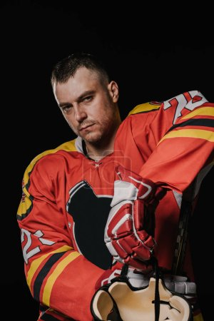 handsome professional ice hockey player looking at camera isolated on black