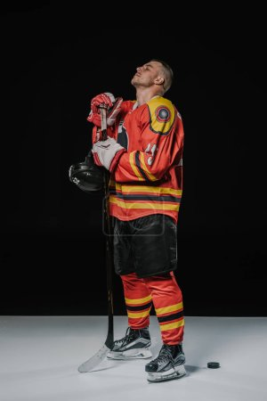 full length view of professional hockey player standing with closed eyes on black