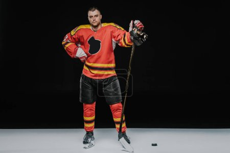 full length view of professional ice hockey player standing with hand on waist and looking at camera on black