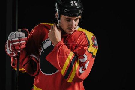 Photo pour Joueur professionnel de hockey adulte tenant bâton de hockey et portant un casque isolé sur noir - image libre de droit