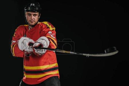 professional hockey player holding hockey stick isolated on black