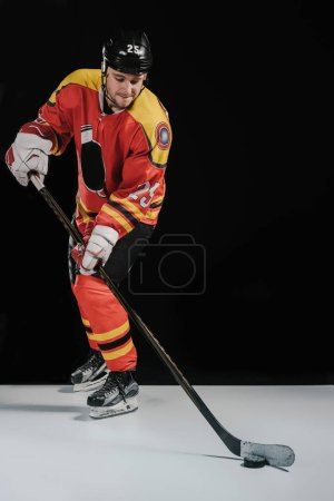 full length view of professional sportsman in skates playing hockey on black