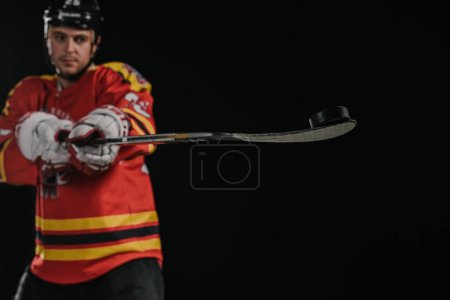 professional young sportsman holding hockey stick isolated on black