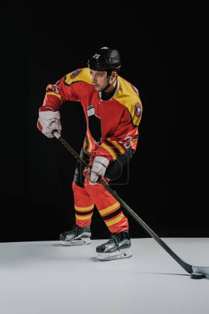 full length view of professional sportsman playing hockey and looking away on black