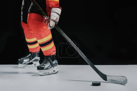 low section of professional sportsman playing hockey on black