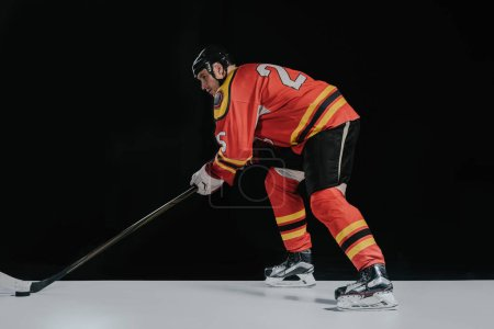 side view of professional sportsman playing hockey on black