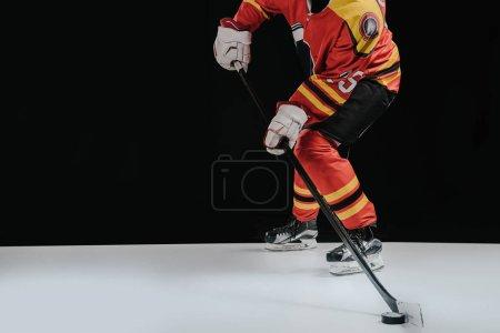 cropped shot of sportsman playing hockey on black