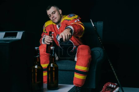 hockey player using remote controller and drinking beer while sitting and watching tv on black
