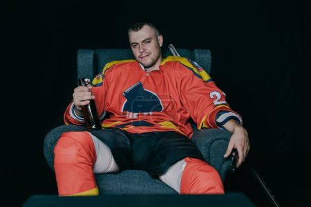 professional hockey player drinking beer and watching tv on black