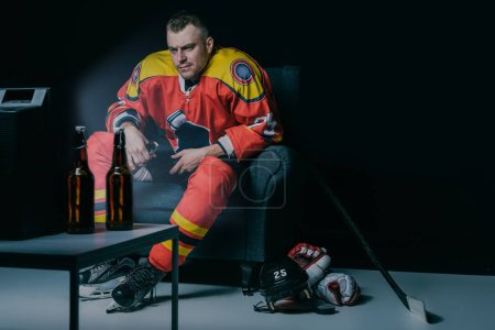 serious young hockey player drinking beer and watching tv while sitting in armchair in black
