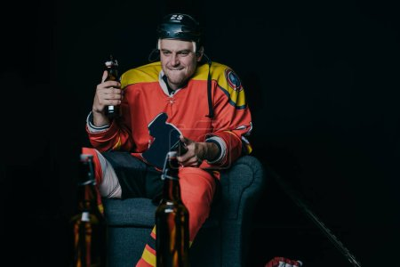 emotional hockey player holding beer bottle and using remote controller while watching tv on black