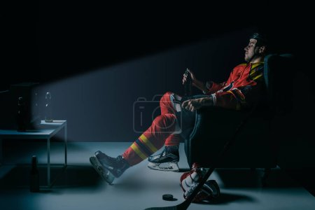 side view of young hockey player drinking beer and watching tv on black