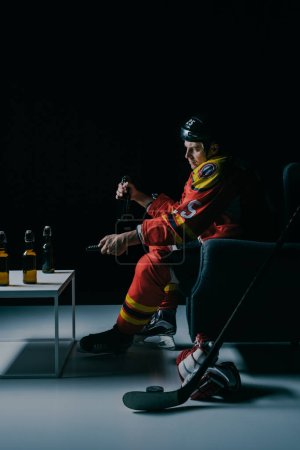 side view of hockey player drinking beer and watching tv on black