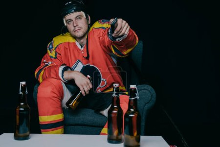 hockey player holding beer bottle and using remote controller while watching tv on black