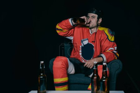 young hockey player drinking beer while sitting in armchair and watching tv on black