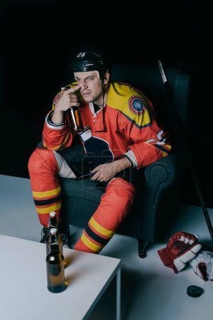 high angle view of hockey player drinking beer and watching tv on black