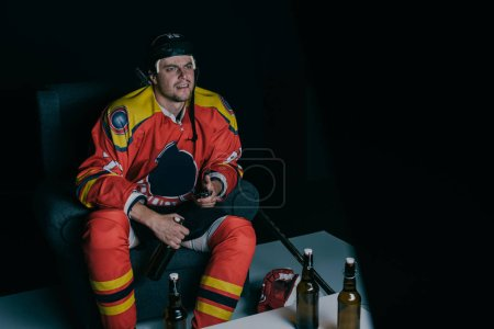 emotional hockey player drinking beer and watching tv on black