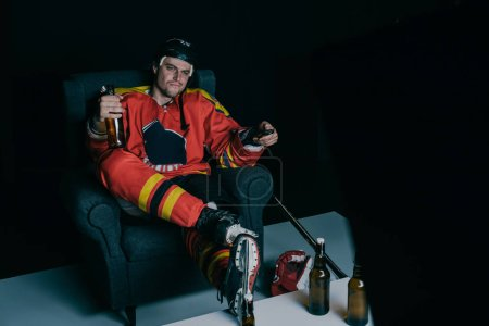 hockey player drinking beer and watching tv on black