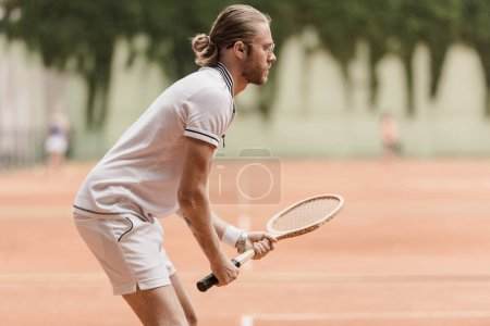 side view of handsome tennis player ready for game with racket at tennis court