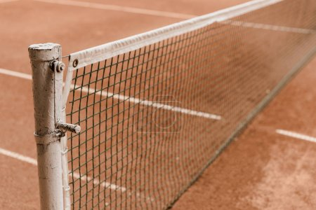 Photo for Brown tennis court with tennis net and marking lines - Royalty Free Image