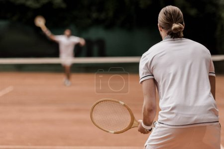 back view of retro styled tennis players during game at tennis court