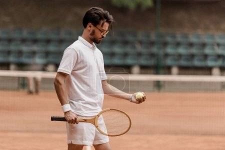 handsome retro styled tennis player standing with tennis ball and racket at court