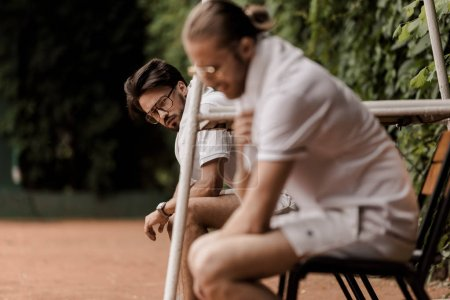 side view of retro styled tennis players sitting on chairs at tennis court