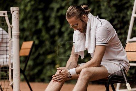 Photo pour Assez beau tennisman assis sur la chaise à un court de tennis - image libre de droit