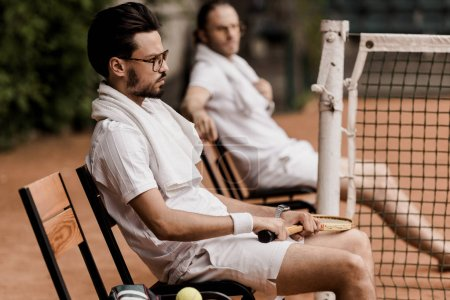 Photo for Side view of retro styled tennis players resting on chairs with towels and rackets at tennis court - Royalty Free Image