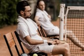 side view of retro styled tennis players resting on chairs with towels and rackets at tennis court