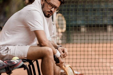 Photo for Serious tennis player sitting on chair with tennis racket at court and looking at camera - Royalty Free Image