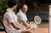 serious retro styled tennis players sitting on chairs with towels and rackets at tennis court