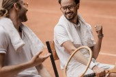 smiling retro styled tennis players sitting on chairs and talking at tennis court