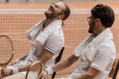 smiling retro styled tennis players sitting on chairs with towels and rackets at tennis court