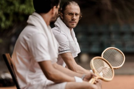 Photo for Retro styled tennis players resting on chairs with towels and rackets at tennis court - Royalty Free Image